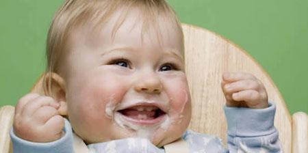 Niño feliz comiendo en su trona